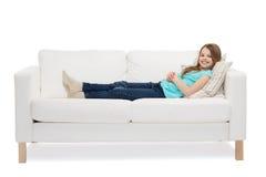 Niña sonriente que miente en el sofá Fotos de archivo