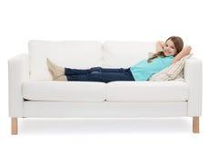 Niña sonriente que miente en el sofá Imagen de archivo