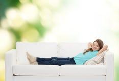 Niña sonriente que miente en el sofá Fotos de archivo libres de regalías