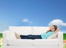 Niña sonriente que miente en el sofá Imagenes de archivo