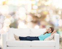 Niña sonriente que miente en el sofá Fotografía de archivo libre de regalías