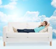 Niña sonriente que miente en el sofá Imagen de archivo libre de regalías