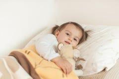 Niña sonriente que miente en su cama que abraza su suavidad del favorito Imágenes de archivo libres de regalías