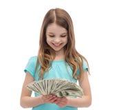 Niña sonriente que mira el dinero del efectivo del dólar Fotografía de archivo
