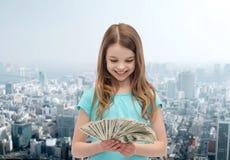 Niña sonriente que mira el dinero del efectivo del dólar Fotos de archivo