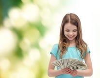 Niña sonriente que mira el dinero del efectivo del dólar Imagenes de archivo