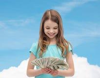 Niña sonriente que mira el dinero del efectivo del dólar Imagen de archivo