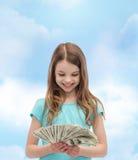 Niña sonriente que mira el dinero del efectivo del dólar Foto de archivo libre de regalías