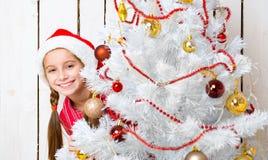 Niña sonriente que mira a escondidas hacia fuera de detrás un árbol del Año Nuevo Imagen de archivo libre de regalías