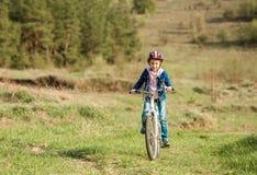 Niña sonriente que monta una bici Foto de archivo libre de regalías