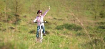 Niña sonriente que monta una bici Fotografía de archivo libre de regalías