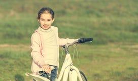 Niña sonriente que monta una bici Fotos de archivo libres de regalías
