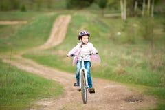 Niña sonriente que monta una bici Imagen de archivo libre de regalías