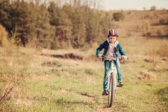 Niña sonriente que monta una bici Foto de archivo