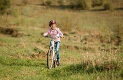 Niña sonriente que monta una bici Imagen de archivo