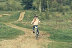 Niña sonriente que monta una bici dada vuelta lejos Imagen de archivo