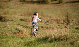 Niña sonriente que monta una bici dada vuelta lejos Foto de archivo