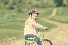 Niña sonriente que monta una bici dada vuelta lejos Imagen de archivo libre de regalías