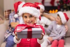 Niña sonriente que ofrece un regalo con sus padres detrás Foto de archivo libre de regalías