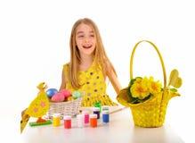 Niña sonriente que pinta los huevos de Pascua Fotografía de archivo libre de regalías