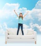 Niña sonriente que salta en el sofá Foto de archivo libre de regalías