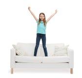 Niña sonriente que salta o que baila en el sofá Fotografía de archivo