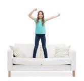 Niña sonriente que salta o que baila en el sofá Imagen de archivo