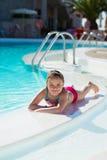 Niña sonriente que se relaja en la piscina Fotografía de archivo libre de regalías