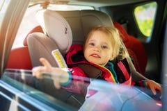 Niña sonriente que se sienta en un asiento de carro del niño fotografía de archivo libre de regalías