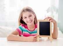Niña sonriente que se sienta en una tabla con la pequeña pizarra vacía Fotos de archivo