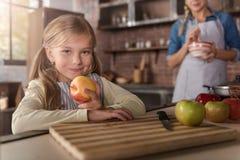 Niña sonriente que sostiene manzanas en la cocina Imagen de archivo libre de regalías