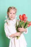 Niña sonriente que sostiene tulipanes Fotos de archivo