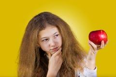 niña sonriente que sostiene una manzana roja imagen de archivo libre de regalías