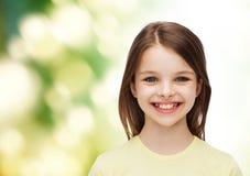 Niña sonriente sobre el fondo blanco Fotografía de archivo
