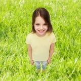 Niña sonriente sobre fondo de la hierba verde Imagen de archivo