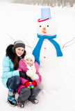 Niña sonriente y mujer joven con el muñeco de nieve en día de invierno Imagen de archivo