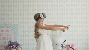 Niña sorprendente feliz que lleva las gafas de la realidad virtual que miran películas o que juegan a los videojuegos metrajes
