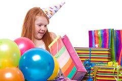 Niña sorprendida con los globos y la caja de regalo Imagen de archivo