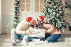Niña sorprendida con los regalos de la Navidad cerca de un árbol de navidad en casa Fotos de archivo libres de regalías