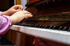 Niña studing para jugar el piano Imagenes de archivo