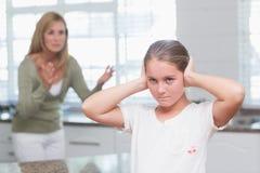 Niña trastornada que cubre sus oídos mientras que su madre que grita fotografía de archivo