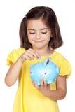 Niña triguena con un moneybox azul Foto de archivo