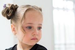 Niña triste hermosa que llora, en ventana del blanco del fondo Foto de archivo libre de regalías