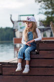 Niña triste que se sienta en un embarcadero y miradas en el río Fotografía de archivo
