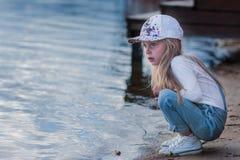 Niña triste que se sienta en un embarcadero y miradas en el río Imagen de archivo