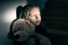 Niña triste que sostiene su oso de peluche - ella siente sola Fotografía de archivo