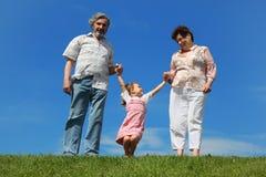 Niña y abuelos que se colocan en césped imagen de archivo