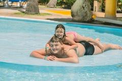 Niña y adolescente que se divierten en piscina del jardín en día caliente soleado Imagen de archivo