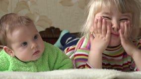 Niña y bebé recién nacido, dos hermanas, TV de observación 4K UltraHD, UHD almacen de metraje de vídeo