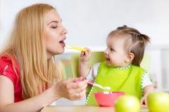 Niña y madre con los alimentos para niños que se alimentan, sentándose en la tabla en cuarto de niños Fotografía de archivo libre de regalías